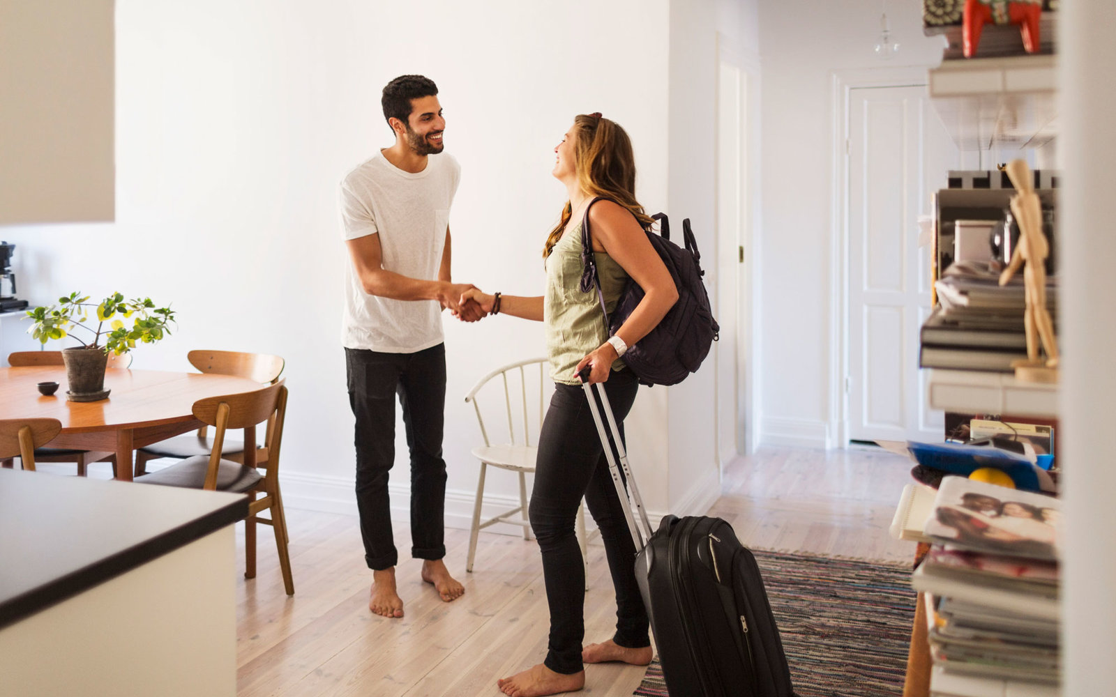 A female guest with a wheely backpack being welcomed by her male host in a light, airy kitchen and diner. They are shaking hands and smiling