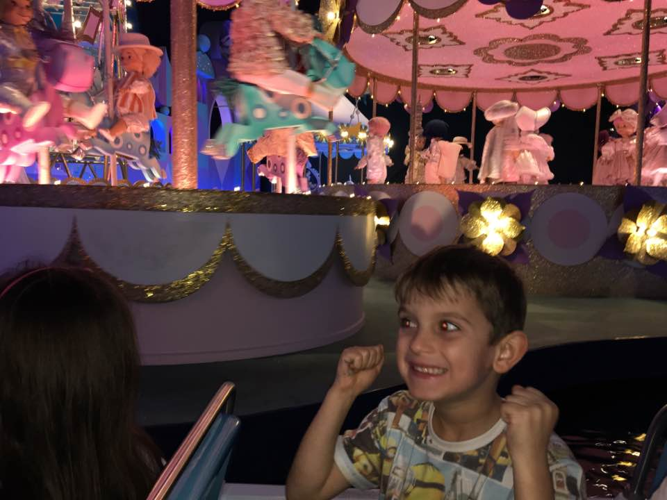 Harvey with a huge smile and fists raised in excitement, on a Disney teacup ride