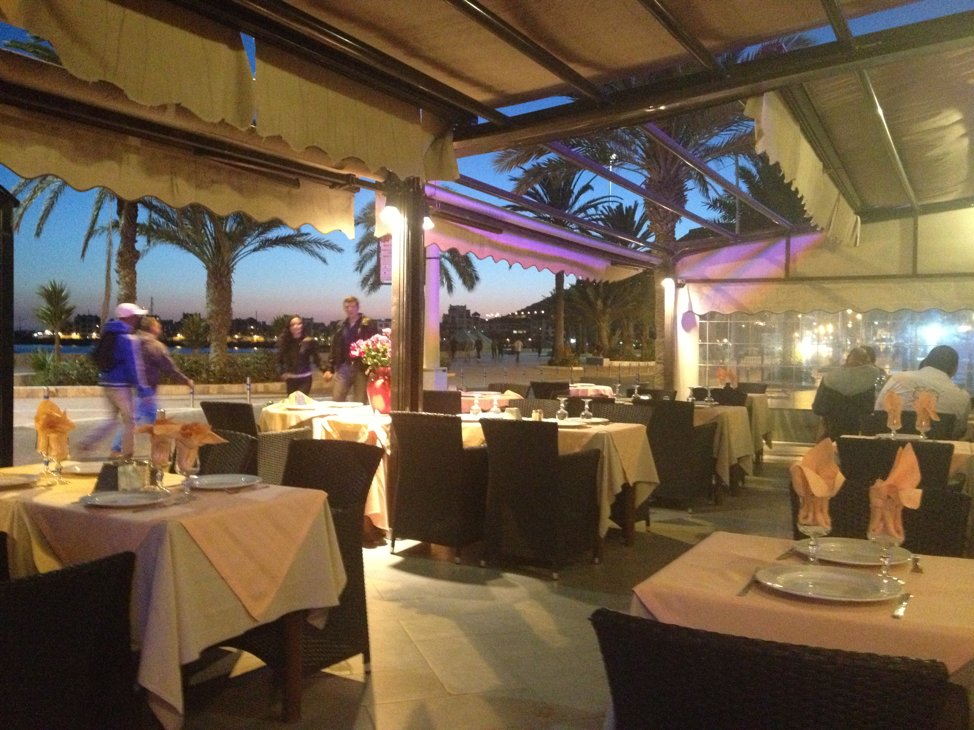 Agadir Ruqantino Restaurant, taken outside with tables, linen cloths, wine glasses filled with folded napkins, overlooking the sea and a pink and blue sky