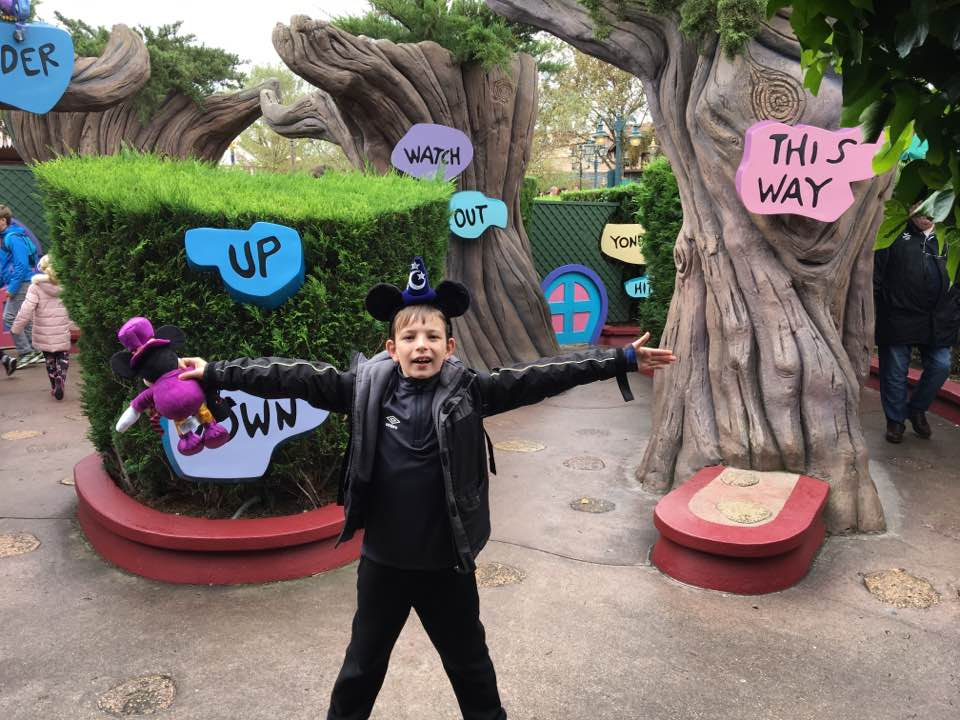Ryan stood with his arms out in front of the Alice in Wonderland maze. He is surrounded by signs saying this way, watch out, up, down, under, yonder. He's holding his Mickey Mouse toy and looking full of energy