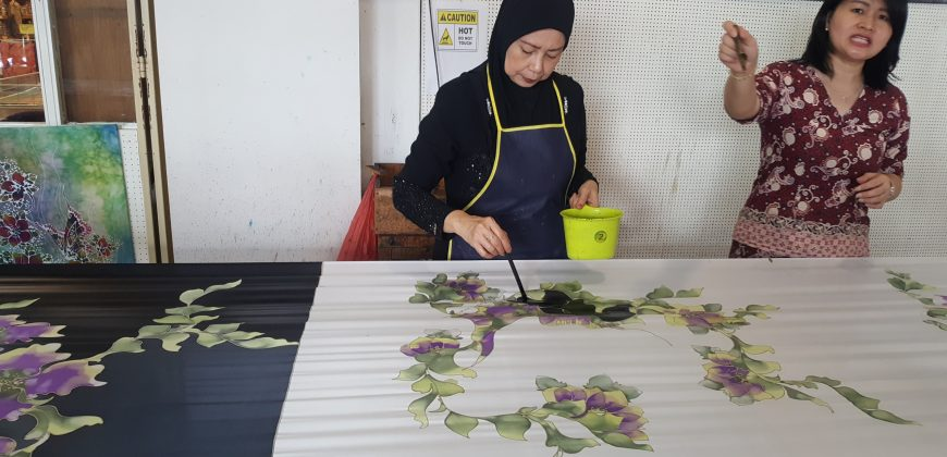 A lady creating batik by painting black around purple and green flowers on silk
