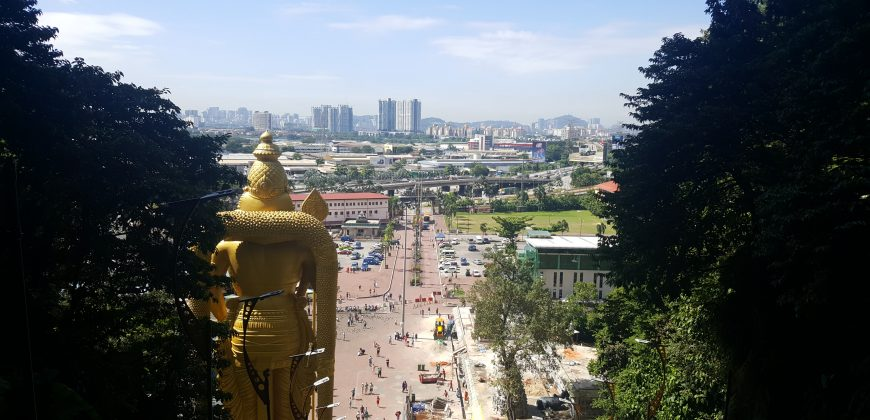 The view from the entrance to the Batu Caves, at the top of the steps, overlooking the gold hindu statue and the city in the background
