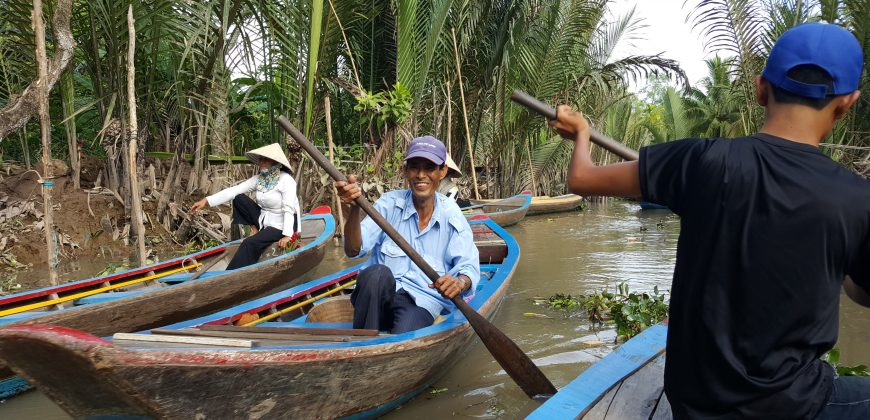 Wooden canoes pass along a muddy canal on the Mekong Delta, bordered by palm trees