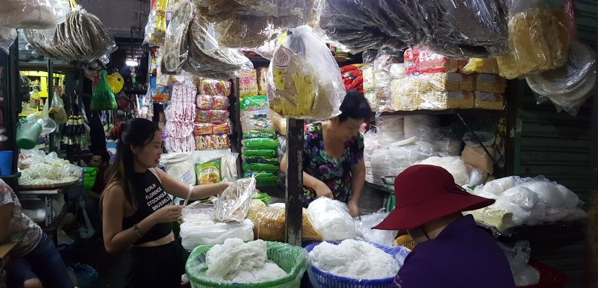 A small indoor stall is laden with baskets and hanging bags of fresh and dried noodles