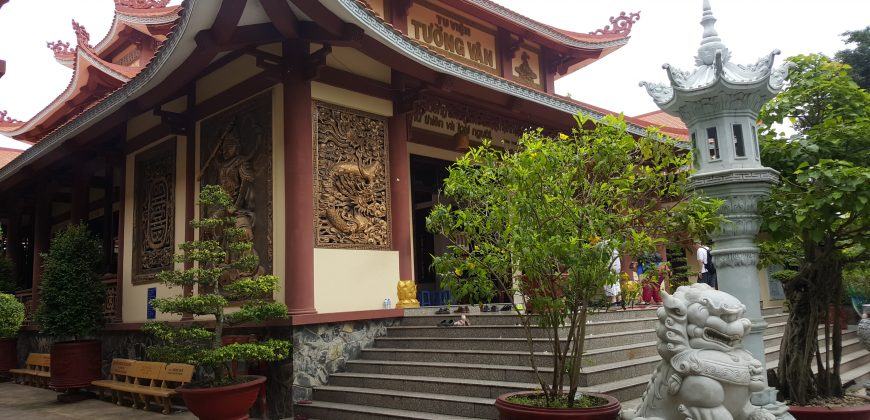 A religious temple with ornate wooden carvings decorating the outside. The temple is in traditional Asian style with pointy roof corners, reds and white. Well tended small trees and shrubs are placed around the walls of the temple.