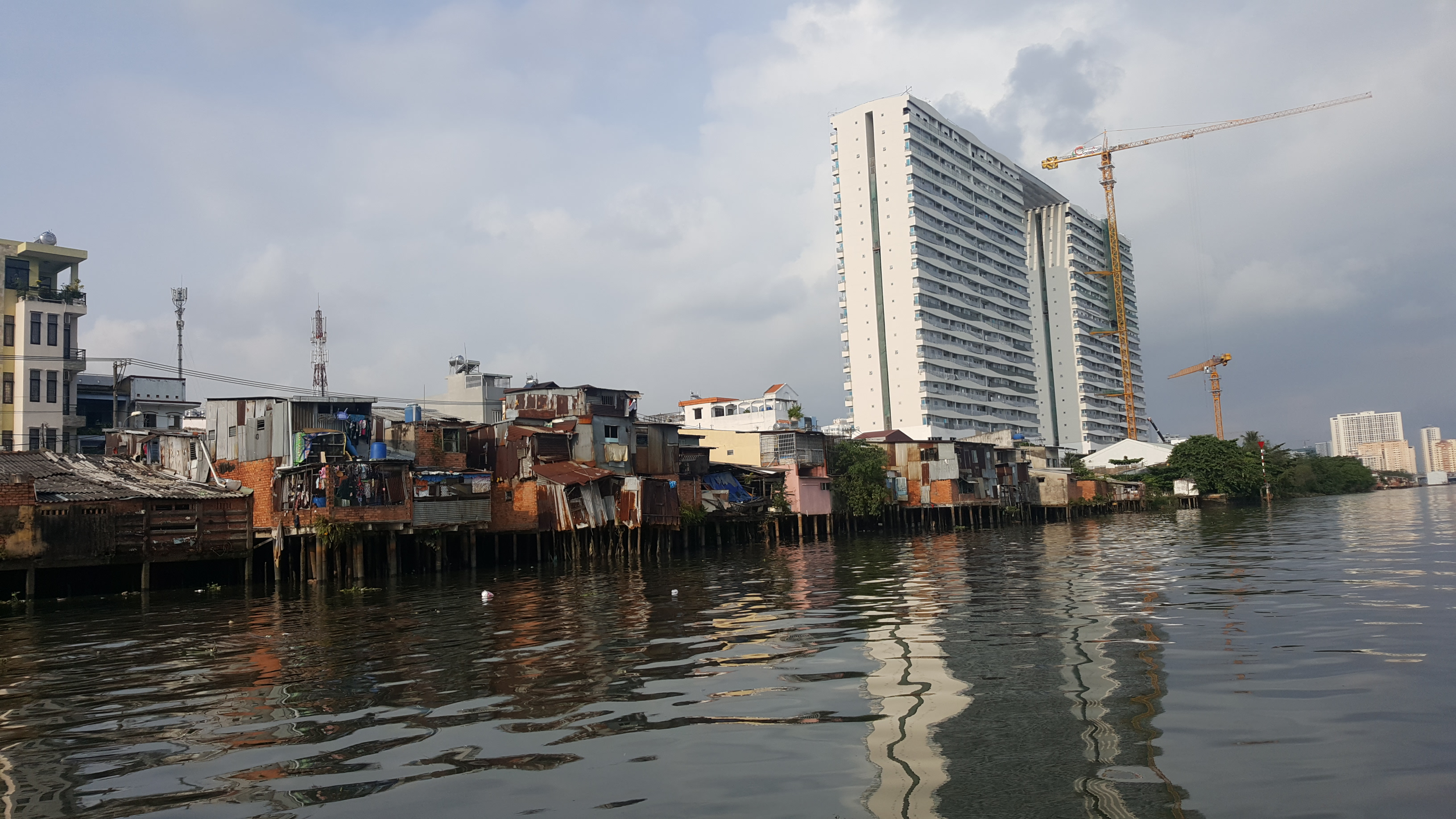 A river view of wooden stilt houses, very run down, with luxury flats under construction in the background