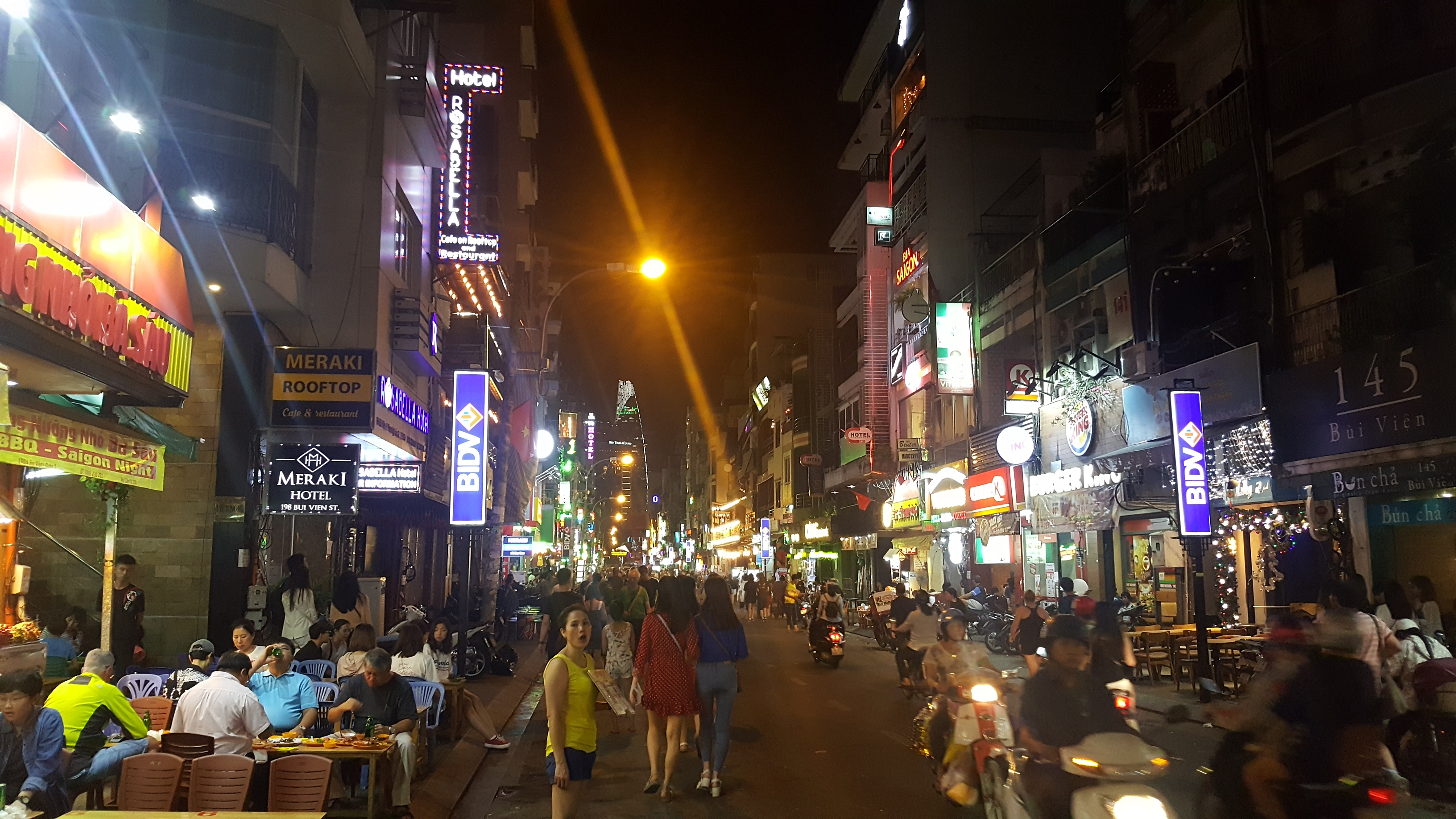 A busy street at night. Lined with bars, restaurants and shops with lit signage, the pavements are full of tables and diners, scooters and pedestrians fill the street.