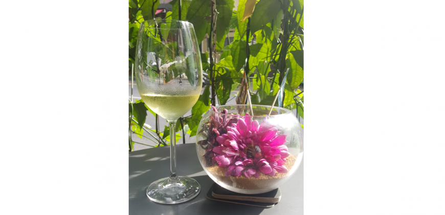 A cold glass of white wine next to a decorative glass bowl with a tropical flower