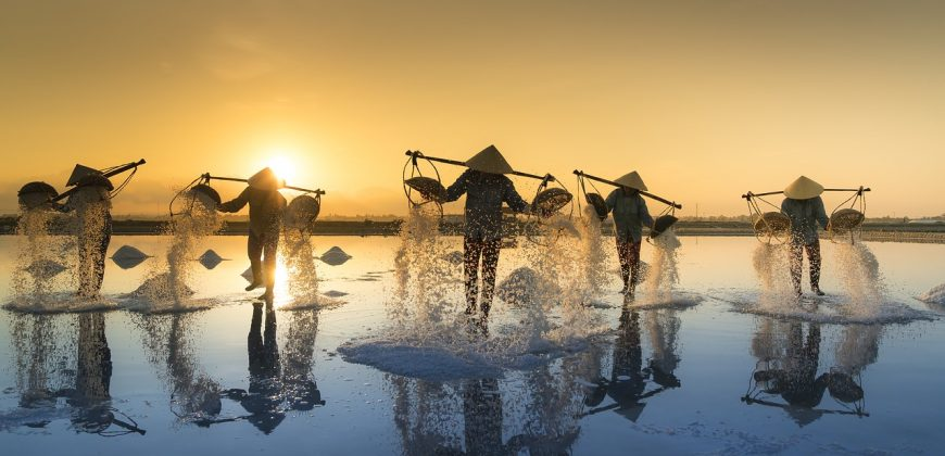 Vietnamese fisherman who seem to be floating on water, with fishing baskets balanced across their shoulders like weighing scales. They are wearing Vietnamese straw hats and the sun is rising behind them