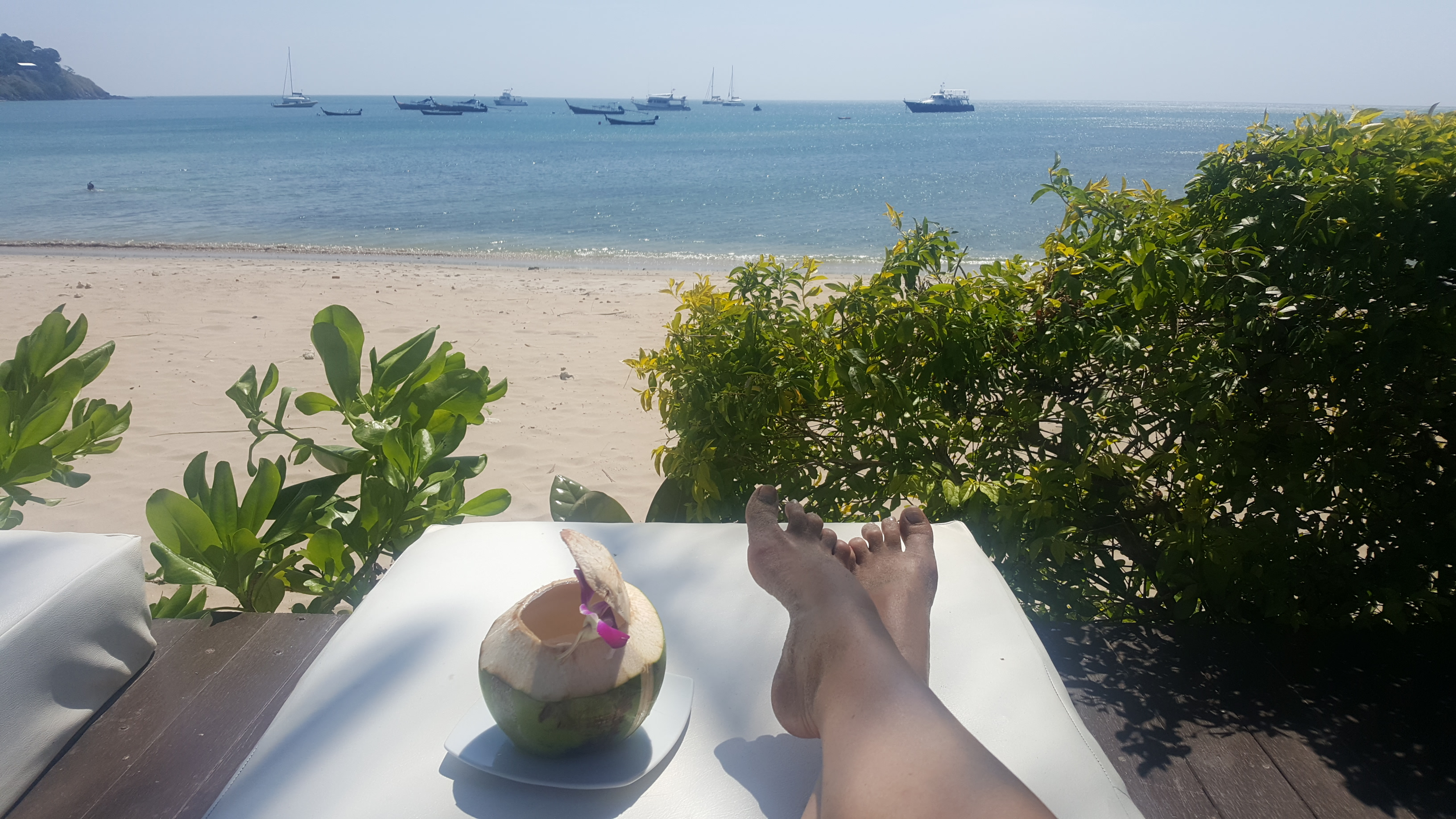 My suntanned feet on a sunlounger with a fresh coconut shell next to me, decorated with a flower. Green tropical shrubs, a sandy beach and blue water dotted with longtail boats are in the background