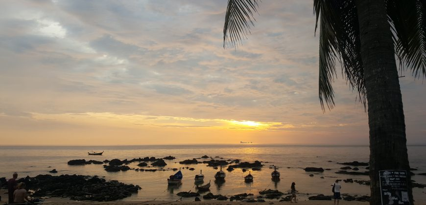 A cloud filled sky with the sun poking through, bright yellow, nearing sunset. In the foreground, small wooden fishing boats flat in the shallow rocky waters