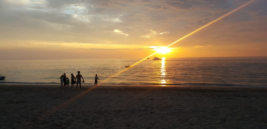 The sun setting over the sea, with a boat just under the sun and a few people walking by