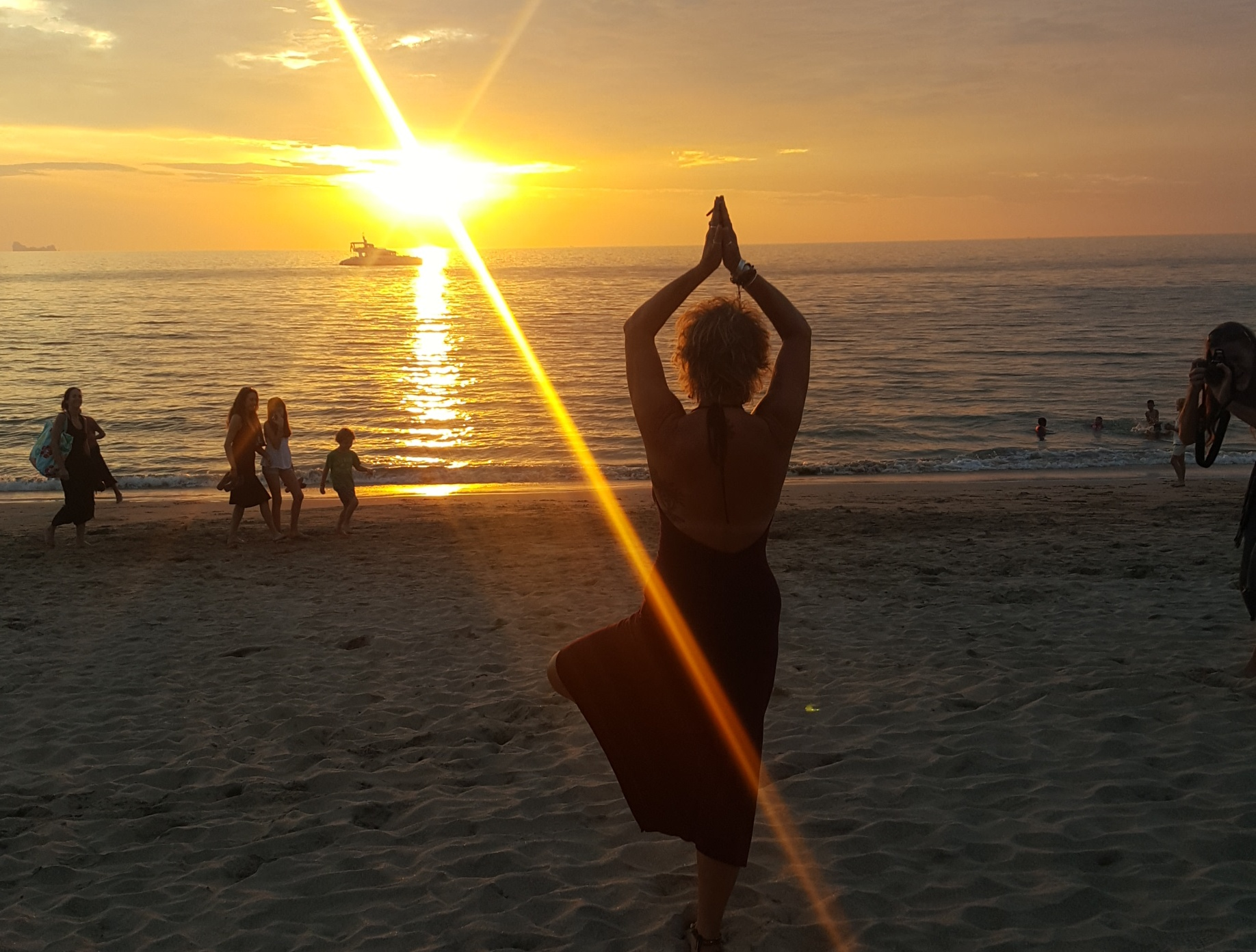 A stunning bright orange sunset with the sun burning bright just above the horizon, a catamaran floats on the water, a few people walk by and in the foreground, a lady is doing a yoga tree pose
