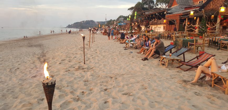 A long stretch of beach with the sea on the left, tiki torches down the middle, a few people sat in deck chairs on the right in front of a row of wooden bars