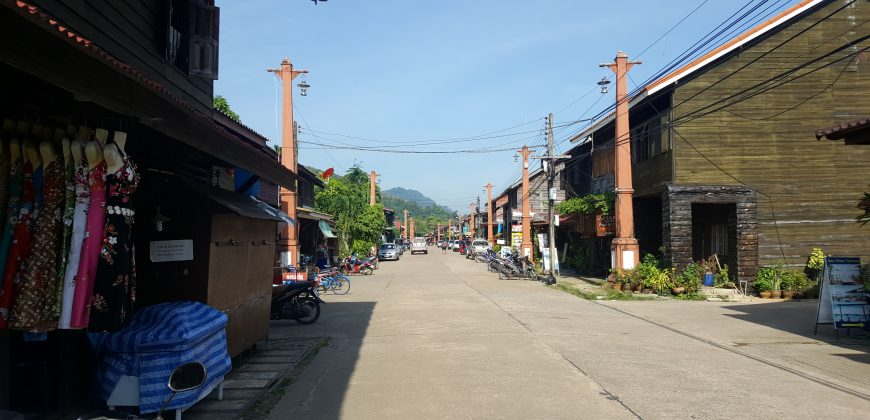 An old looking high street of wooden buildings with trees and a hill in the background