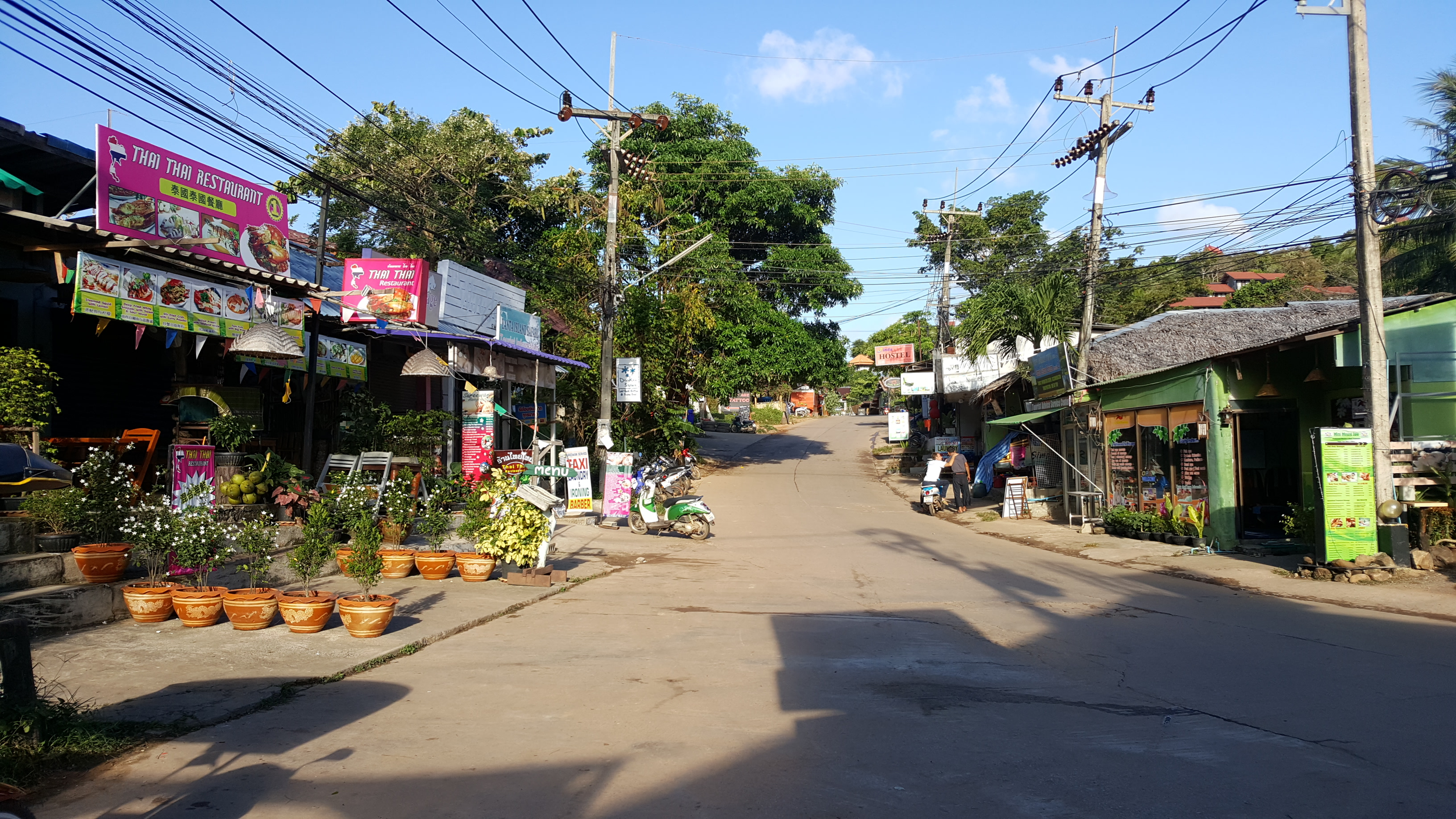 A few shops and restaurants border the road with no passing traffic. The buildings are basic, single storey structures with plant pots and bright signs outside
