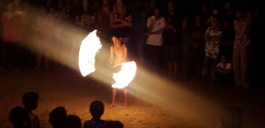 A boy juggles a fiery baton on the beach